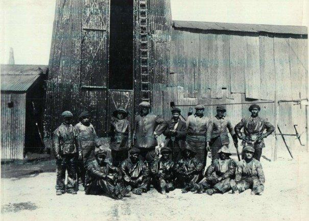 Operarios y jefe frente a torre de petróleo.