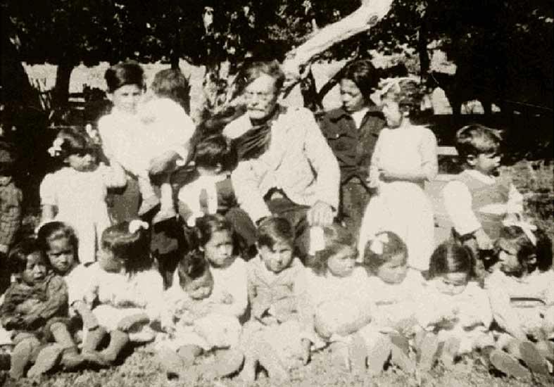 Don Juan Benigar rodeado de pequeños alumnos de una escuela rural.