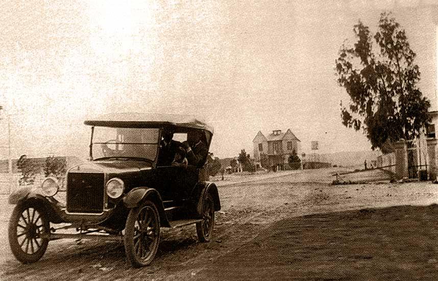 """Auto circulando por la Av. Argentina - Neuquén Capital - 1913 - Al fondo, """"le Chateau Gris"""", sede de la gobernación del territorio del Neuquén, a pocos metros del lugar que actualmente ocupa el monumento a San Martín."""