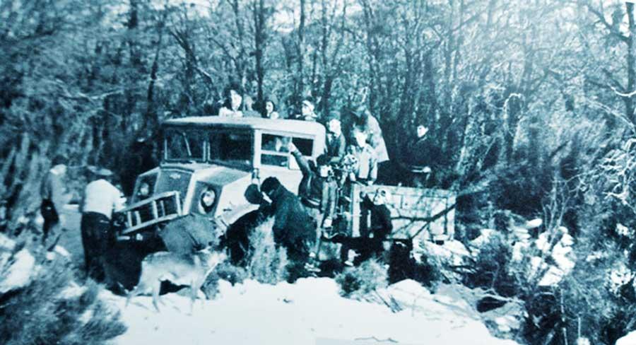 Atascado en la nieve, el primer vehículo que trasladó a los esquiadores, un Chevrolet canadiense.